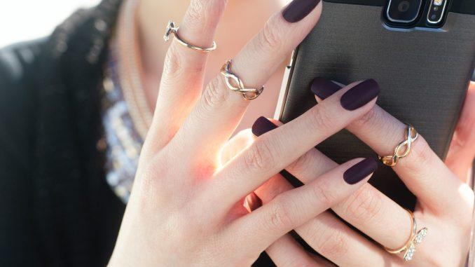 Person holder telefon med sorte negle